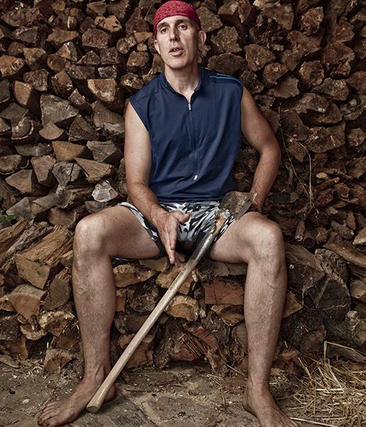 Christopher McDougall, (barefoot) runner and author of the national bestselling book Born to Run, sits atop a pile of chopped wood, ax at the ready, barefoot at his home in Pennsylvania (Photo by Bill Cramer)