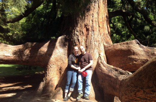 A photo of Jen K. and her husband in the Christchurch Botanic Gardens on the south island of New Zealand.  They are standing in front of a massive Atlas Cedar tree.  KSO Treks.