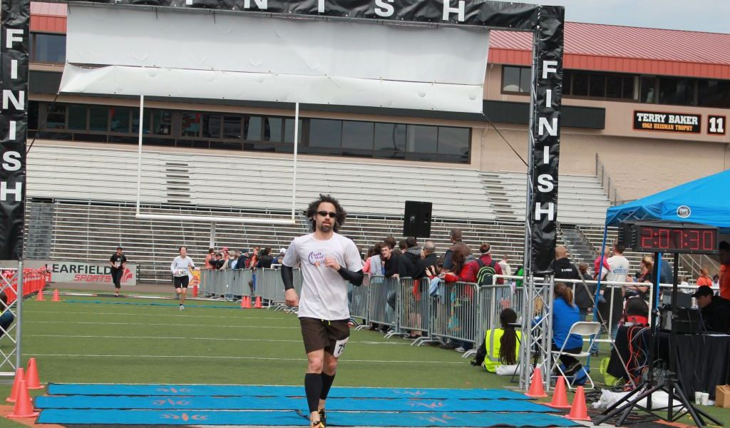 Jay crosses the finish line in the Corvallis Half Marathon - on the Oregon State football field in 2:07 sporting some hornet-colored Dash Soft Start RunAmocs.