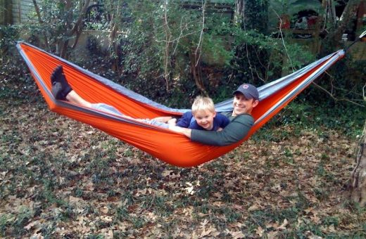 Josh kicks back and relaxes with his son on his hammock in his black KSO Vibram Five Fingers.