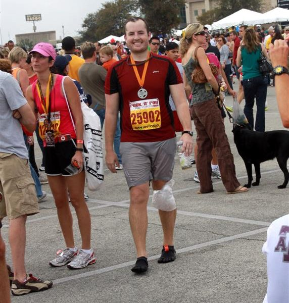 Tyler stands before the San Antonio Rock'n'Roll Marathon & 1/2 sign post-race.